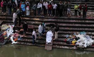 两名当地女子趴在桥上观看葬礼。当地时间28日,尼泊尔宣布将为在地震中遇难和受伤的人员设立为期3天的国家哀悼日。 澎湃新闻记者 李坤 图