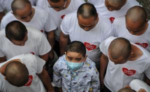 """2015年6月,在合肥徽州大道与环城路交口附近,11位理着光头的父亲守着一辆小车卖瓶装水。他们穿着白T恤,身上还贴着""""白血病患儿光头老爸团""""标识。CFP 图"""