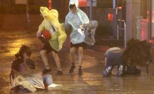 """2015年8月7日,台湾省台北市,台风""""苏迪罗""""逼近,几名市民顶风冒雨前行,其中两人被吹倒在地。"""
