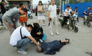 老人倒地后,过路市民纷纷拍照作证后才去上前帮助老人擦拭血迹。 CFP 图
