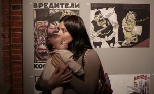 一位年轻的母亲怀抱婴儿前来观展。 东方IC 图