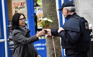 当地时间2015年11月14日,法国巴黎发生恐怖袭击事件的Charonne路,一位市民正在请求警察将手中的鲜花摆放在犯罪现场,用以悼念死难者。