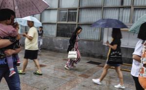 2016年6月12日,上海火车站,一名忘记带伞的女子在人群中疾跑躲雨。上海中心气象台于07时25分发布暴雨蓝色预警:受较强的降水云团影响,预计未来12小时内本市大部地区累积降水量将达50毫米以上,请注意防范。  澎湃见习记者 韦毅 图
