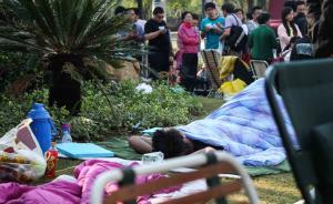 """2016年9月24日,上海宝山区真朋路,一名居民带着被褥躺在草坪上等待排队购买停车位。22日中午,物业公司发来消息称,""""按销售部门通知,我们尊重业主自发组织的自发行为,做好现场秩序维护和保洁工作。9月24日9点开盘将依照先后顺序,先到先得,选完为止……"""",而21日晚,已有百余名业主在认购处外排队。 澎湃新闻见习记者 韦毅 图"""