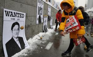 """当地时间2017年1月21日,韩国首尔,韩国民众计划进行第13次烛光集会,向墙上贴着的三星电子副会长李在镕等""""干政门""""涉事人的图片投球出气。视觉中国 图"""
