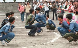 """1986年夏,四川成都西南民族学院的少数民族传统体育运动会上,选手在""""蹲斗""""比赛中。""""蹲斗""""是彝族青年模仿雄鸡斗架的一种运动,比赛选手下蹲跳跃,互相以肩相撞,被撞倒者为输。"""