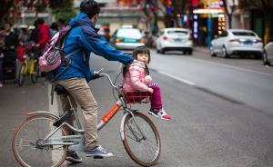 """共享单车为人们的出行提供了不少便利,成为城市街头一道亮丽的风景线。而如今,有不少送孩子上下学的家长,将共享单车变成了""""亲子单车""""。图为2017年3月6日,广东省广州市,一名男子骑共享单车载着孩子,车筐变成了""""儿童座椅""""。 本图集图片均来自 东方IC"""