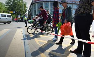 """4月28日,湖北襄阳,为减少市民在过马路时可能会出现的不文明行为,从4月28日开始,襄阳城区一些路口设立了""""过马路绳器"""",红灯亮起时,交通协管员和志愿者就会拉起绳子进行劝导,效果明显,今后类似措施将在全市重点路口推广。图为鼓楼警务平台交通协管员在十字路口拉绳阻止行人和非机动车闯红灯。  视觉中国 图"""