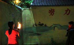 """前几年,因陪考家长在""""神树""""下烧香险酿火灾。今年,为了保护古树,当地政府采取各种措施,却依然没能阻止家长易地焚香。图为2017年5月26日晚, 陪读家长来到""""神树""""附近的围墙下焚香祈祷。 视觉中国 资料图"""