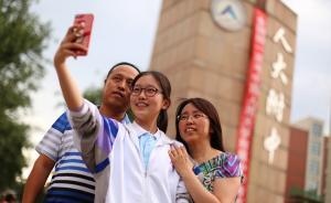 2017年6月8日,北京,人大附中考场,最后一科考完。陪考家长手捧鲜花,举高相机,场外等待学子归来,考生与家长在校门口合影留念庆祝。 东方IC 图