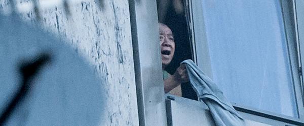 英国《每日邮报》报道,可以听到受困者尖叫求救,也有些人用床单做成绳子,试图垂降到地面。《卫报》稍早前报道称,大厦内可见一名男子向窗外挥舞毯子求救。图为一名受困者站在大楼窗边。东方 IC 图