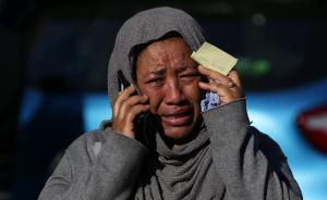 一名女子在寻找失踪的亲人,这名失踪者有可能火灾时在大楼内。视觉中国 图