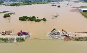 据民政部门统计,截至7月4日,湖南暴雨致使长沙、株洲、湘潭、邵阳等13市(自治州)99个县(市、区)共692.1万人受灾,27人死亡,7人失踪,直接经济损失达190.3亿元。图为7月3日,湖南长沙,因连续强降雨和长时间高水位浸泡,长沙县黄兴镇高塘村画田撇洪渠出现外坡崩塌,外坡上部出现散浸集中,出现溃口。险情发生后,工作人员火速进行抗洪抢险工作,大卡车不舍昼夜填石堵溃口拦洪。东方IC 图