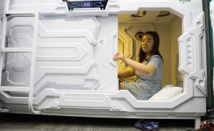 """据悉,该太空舱中午时段为使用高峰期,晚间则成为加班一族过夜休息的""""旅馆""""。图为7月9日,北京中关村创业空间""""共享睡眠""""太空舱内一名""""睡客""""准备关闭舱门进行休息。 视觉中国 图"""