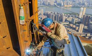 """2017年7月22日,既是""""大暑日"""",又是中伏第一天,武汉骄阳似火进入煎烤模式,最高气温达37℃。置身在建的中国第一高楼——武汉绿地中心,460米高的建设施工顶模层,温度超过40℃。每天有1000多名建设者在工地忙碌着。项目严格避开中午最热时段,上午工作时间6点到11点,下午3点到6点。现场工人都是满头大汗,特别是电焊工,全身捂得严实,更加闷热。图为:2017年7月22日,电焊工陆书文在高空焊接施工。  本图集图均为 视觉中国  图"""