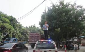 暖闻 电缆掉下悬半空致拥堵,佛山交警站车顶用竹竿托举
