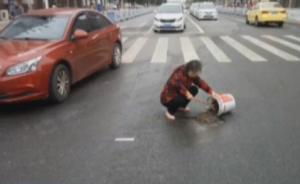 7旬老人自带水泥铲子,车流中填补路坑