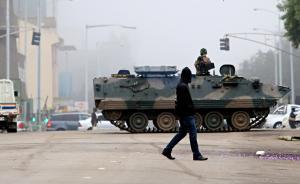 """当地时间2017年11月15日,津巴布韦哈拉雷,人们从装甲车前走过。津巴布韦""""政变"""",军方持续封锁通往政府的道路,总统穆加贝被扣。目前,津军方已进驻津巴布韦国营电视台ZBC,随后军方发布电视讲话否认发动军事政变,并表示总统穆加贝目前安全。15日1时左右,津巴布韦首都哈拉雷市区传出2至3声疑似爆炸声,目前局势已趋于平静。视觉中国 图"""