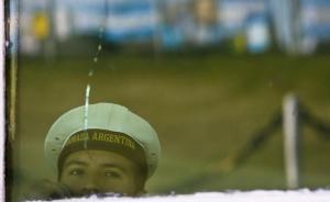 当地时间11月23日,阿根廷普拉塔海军基地,一名海军透过玻璃窗望向室外。  东方IC 图