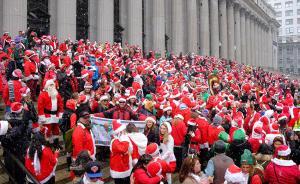 当地时间2017年12月9日,美国纽约,纽约迎来今年第一场降雪,恰逢民众举行圣诞老人大集会庆祝活动。 视觉中国 图