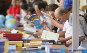 书展上一位白发苍苍的老人在挑书。